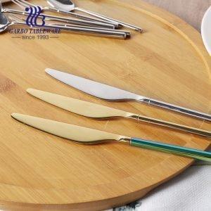 Имеющийся на складе обеденный нож серебристого и золотистого цвета с длинной ручкой